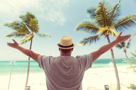 Happy Tourist man in summer hat with outstretched arms enjoy vacations and watching the sea view at balcony, caribbean nature background Archivio Fotografico