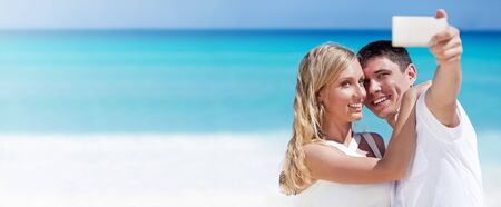 Happy couple taking a photo on a beach with turquoise sea background. Travel vacation concept. Panorama banner Foto de archivo
