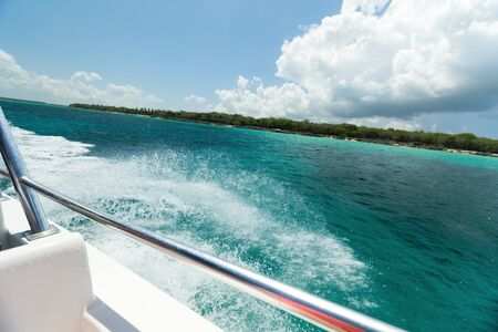 Catamaran boat sailing in Caribbean sea, view from motor yacht in motion with splash and waves. Maritime cruising holiday
