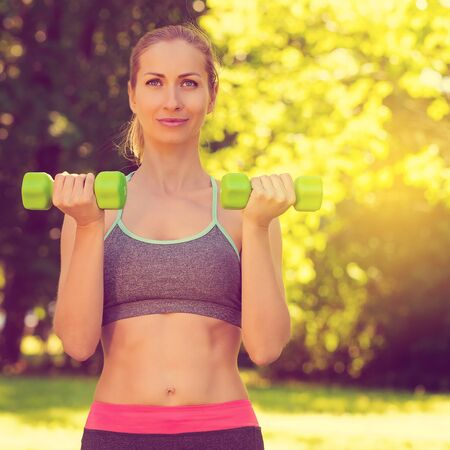 Young slim woman doing fit activity and training with dumbells,outside on green grass at park. Fitness, sport and healthy lifestyle