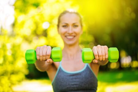 Young slim woman doing fit activity and training with dumbells. Front green dumbells raise in shoulder press exercise outside at park. Fitness, sport and healthy lifestyle