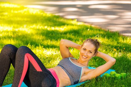 Young slim woman doing fitness activity and training outside on green grass at park. Fitness, sport and healthy lifestyle