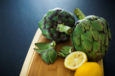 Fresh artichokes on wooden cutting board with lemons, cooking process, nobody 免版税图像