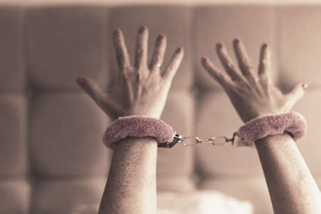Pink sexy fluffy handcuff locked on female wrists, closeup. Erotic sex game with sexual bdsm toy in bedroom interior, no face