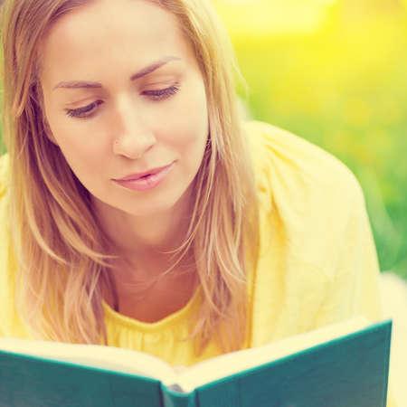 Portrait of blond woman lying on grass and reading on summer park background. Reklamní fotografie