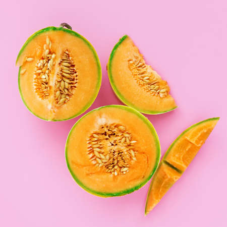 Yellow cantaloupe melon on pink colorful background. Summer food concept composition, flat lay