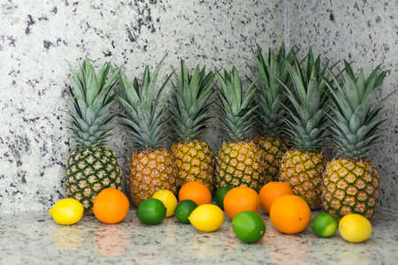 A lot of tropical fruits on table top, pineapples and citrus in kitchen interior, food backgound concept 免版税图像