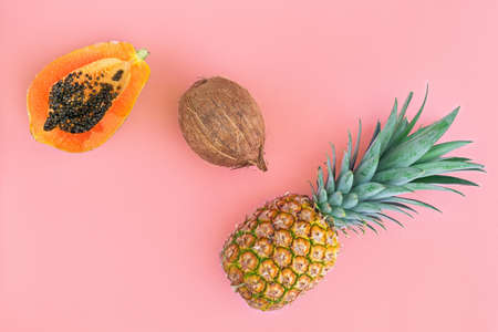 Tropical fruits on pink color background. Pineapple, papaya, and mango flat lay. Summer food concept