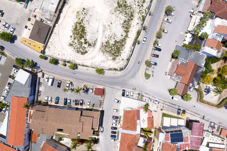 Aerial view from drone on street with houses and asphalt roads. Tropical town
