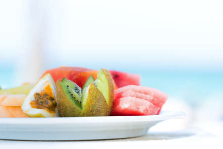 Snack with fresh tropical fruits on sea background with copy space