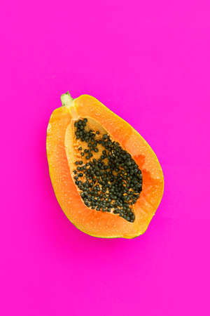 Top view of ripe half cut papaya on color background. Healthy summer food concept with tropical fruits, flat lay Standard-Bild
