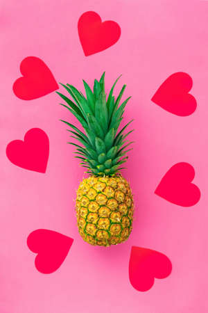Whole pineapple tropical fruit in love with red hearts on pink pastel background, summer concept, flat lay. Romantic greeting card for vegetarians