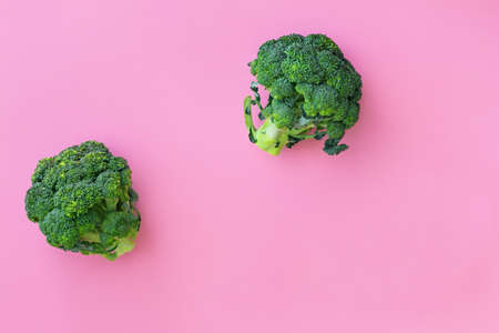 Fresh green broccoli on paper pink background. Organic summer vegetables for diet food concept, flat lay