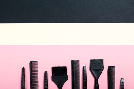 Hairdressing tools with copy space, combs and bleach brushes on pastel colored paper background, top view and flat lay Foto de archivo