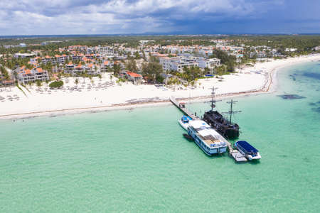 Aerial view from drone on caribbean sea coastline with resorts and wooden pier. Tropical destinations. Summer vacations