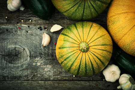 Patty pan, zuchinni, pumpkins and spices on old wooden table. Fresh seasonal autumn vegetables concept.