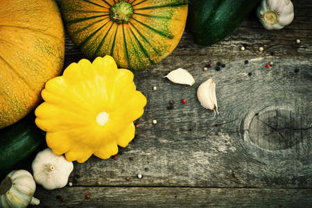Patty pan, zuchinni, pumpkins and spices on old wooden table. Fresh seasonal autumn vegetables concept. Stock fotó