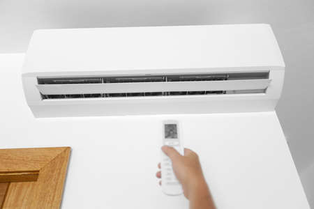 Flat air conditioner on white wall in room interior. Man pushing button on remote. Setting temperature