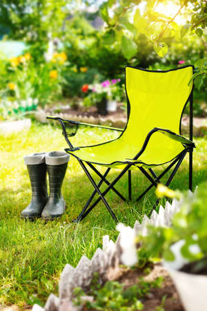 Green folding textile chair for rest and rubber boots on grass in garden at summer day, nobody Reklamní fotografie - 153700077