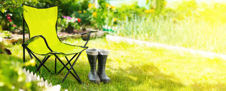 Green folding textile chair for rest and rubber boots on grass in garden at summer day, nobody Reklamní fotografie - 153700093