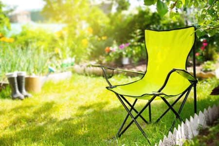 Green folding textile chair for rest in garden at summer day, nobody. Gardening tools - rubber boots and water can on background Reklamní fotografie - 153700091