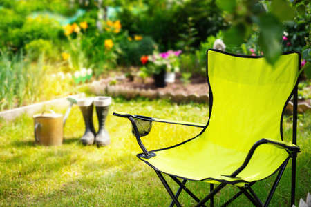 Green folding textile chair for rest in garden at summer day, nobody. Gardening tools - rubber boots and water can on background Reklamní fotografie - 153700095