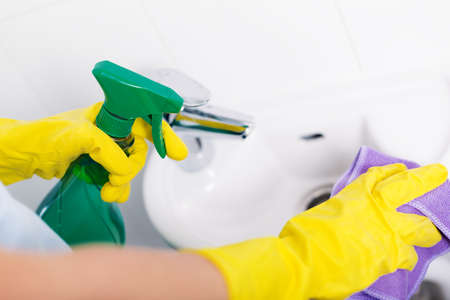 Hand of woman in protective gloves cleaning tile using microfiber cloth and detergent, concept of housekeeping and hygiene,