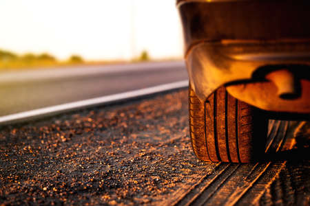 Crop of car wheel closeup with country asphalt road background at sunset. Nobody Reklamní fotografie - 153664151