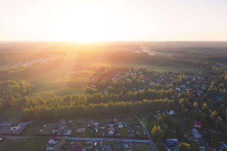 Country village in field near forest. Sunset. Drone view Reklamní fotografie - 153664196