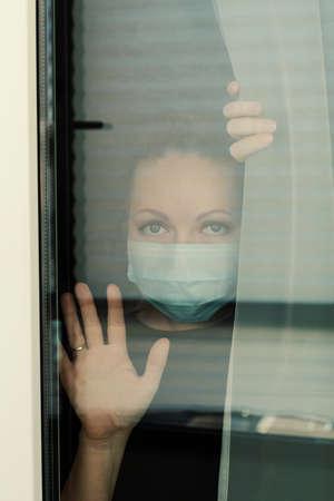 COVID-19 Pandemic Coronavirus Lockdown. Sad woman on quarantine in medical mask on face looking through the window. People on self isolation concept Reklamní fotografie - 153664198
