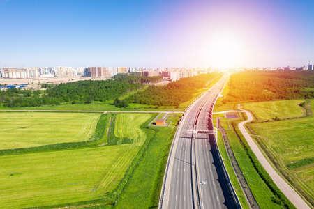 Asphalt ringroad around big city. Speedway through field near forest Reklamní fotografie - 153664226