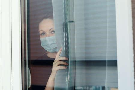 COVID-19 Pandemic Coronavirus Lockdown. Sad woman on quarantine in medical mask on face looking through the window. People on self isolation concept