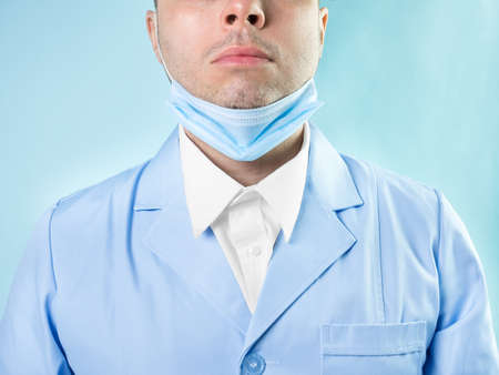 Doctor in professional medical suit with stethoscope and protective medic mask, closeup