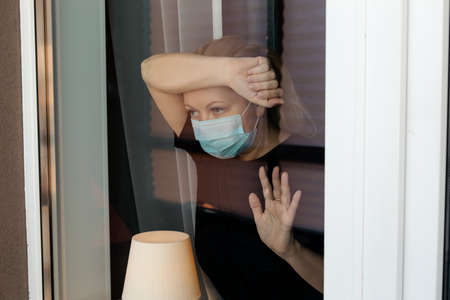 COVID-19 Pandemic Coronavirus Lockdown. Sad woman on quarantine in medical mask on face looking through the window. People on self isolation concept Reklamní fotografie - 153664320