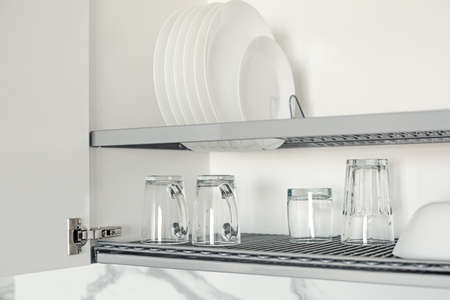 Dish drying metal rack with white clean plates, closeup. Tableware inside kitchen cabinet