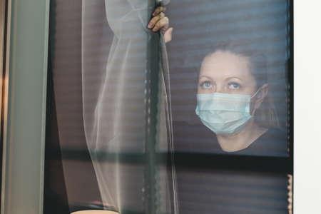 COVID-19 Pandemic Coronavirus Lockdown. Sad woman on quarantine in medical mask on face looking through the window. People on self isolation concept Reklamní fotografie - 153664325
