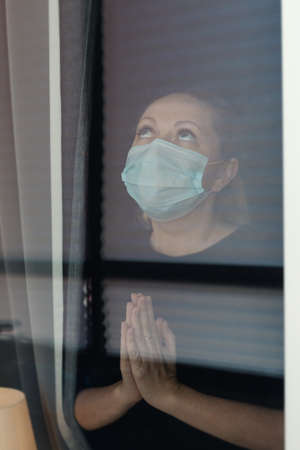 COVID-19 Pandemic Coronavirus Lockdown. Sad woman on quarantine in medical mask on face looking through the window. People on self isolation concept Reklamní fotografie - 153664342