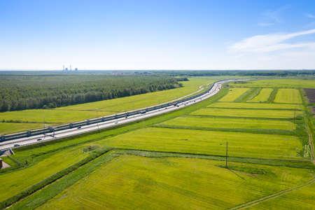 Asphalt ringroad around big city. Speedway with cars through green field near forest Reklamní fotografie