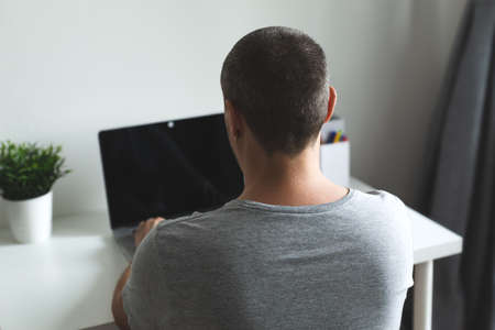 Freelancer working at home office, man using laptop at workplace inside his apartment, Back view and no face, remote work and pandemic isolation concept