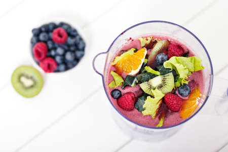 Top view of blending fruits ingredients for smoothie in blender, macro with copy space