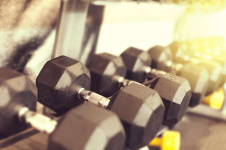 Black color dumbbell weights in fitness center. Gym equipment. Blurred background for copy space. Shallow depth. Reklamní fotografie