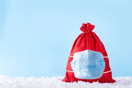 Red christmas present bag with gifts in protective medical mask on snow over blue background. New Year celebration in epidemic time