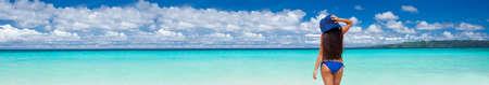 Woman in blue summer hat on beach. Back view. Travel destinations. Summer vacations Reklamní fotografie