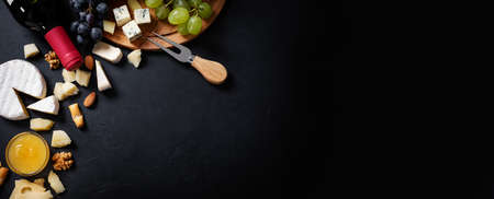 Menu frame with different types of cheese, honey, grapes and wine on black background. Top view, flat lay with copy space