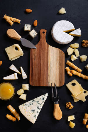 Empty wooden cut board arranged different types of cheese on black background. Top view Reklamní fotografie