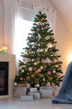 Beautiful decorated evergreen shiny fir tree with white and pink color balls with garland lights. Christmas scandi decoration at house. New Year Hygge interior, no people.