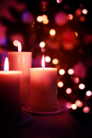 Christmas burning candles on garland lights blurred background, decorative New Year card with copy space Reklamní fotografie