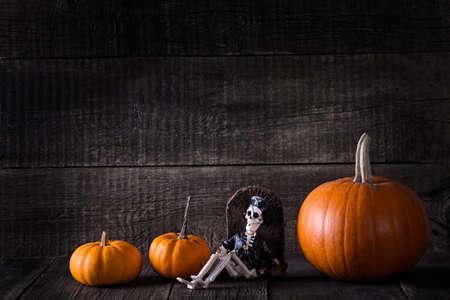 Halloween pumpkins and skeleton toy on wooden background. Autumn background Reklamní fotografie