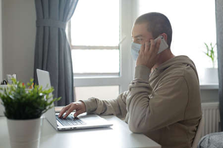 Man in medical mask working at home with laptop, housework quarantine isolation during pandemic coronovirus. Covid-19 concept