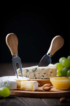 Different types of cheese on served wooden board on dark background with copy space Reklamní fotografie